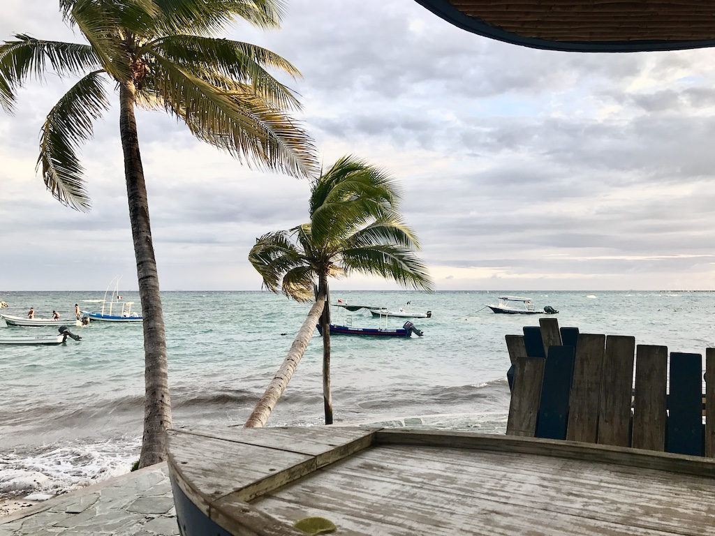 Boat shaped table overlooking Caribbean sea and anchored boats in Playa del Carmen