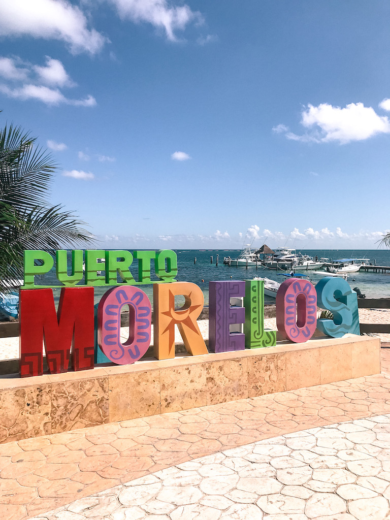 Colorful Puerto Morelos sign with ocean in the background