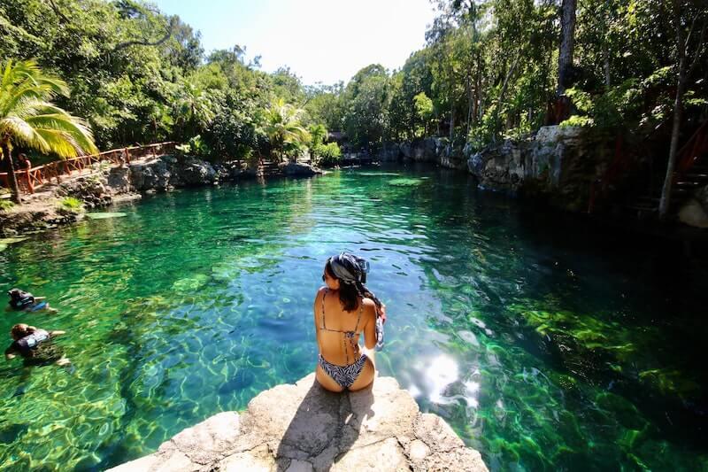 Solo female traveler sitting next to cenote in Riviera Maya, Mexico