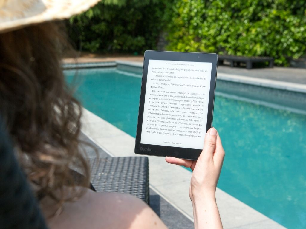 female traveler reading a kindle by the pool