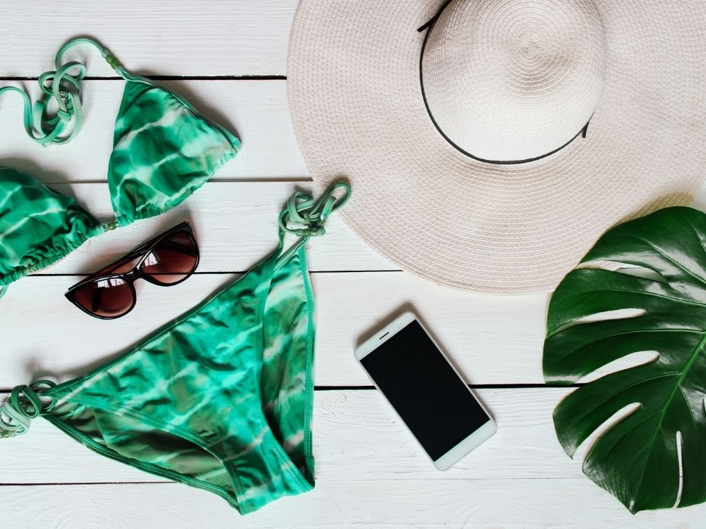 flatlay image of triangle string bikini with cell phone, sunglasses, and a sun hat